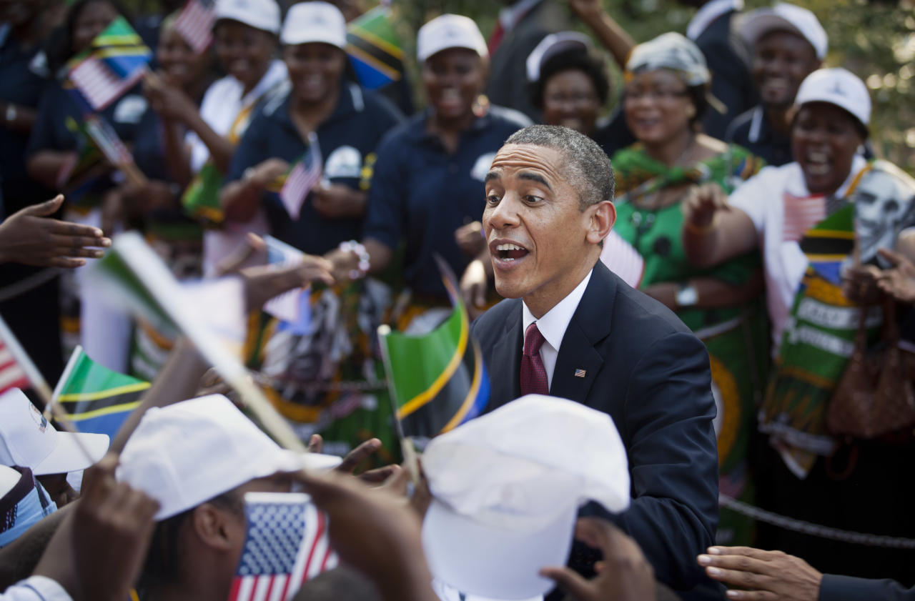 U.S. President Barack Obama shakes the hands of a line of women stationed to welcome his arrival at State House in Dar es Salaam, Tanzania Monday, July 1, 2013. Teeming crowds and blaring horns welcomed President Barack Obama to Tanzania's largest city, where the U.S. president's likeness is everywhere as he arrived on the last leg of his three-country tour of the African continent. (AP Photo/Ben Curtis)