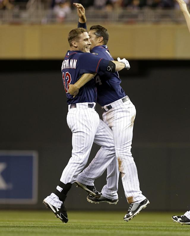 Minnesota Twins' Trevor Plouffe, right, and Chris Herrmann celebrate Herrmann's walkoff off Chicago White Sox pitcher Ramon Troncoso in a baseball game, Thursday, Aug. 15, 2013 in Minneapolis. The Twins won 4-3. (AP Photo/Jim Mone)