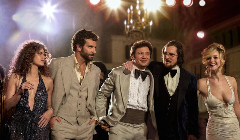 """This film image released by Sony Pictures shows, from left, Amy Adams, Bradley Cooper, Jeremy Renner, Christian Bale and Jennifer Lawrence in a scene from """"American Hustle."""" The film received 13 nominations for the Broadcast Film Critics Association's 19th Annual Critics' Choice Movie Awards airing Jan. 16, 2014 on the CW network. (AP Photo/Sony - Columbia Pictures, Francois Duhamel)"""
