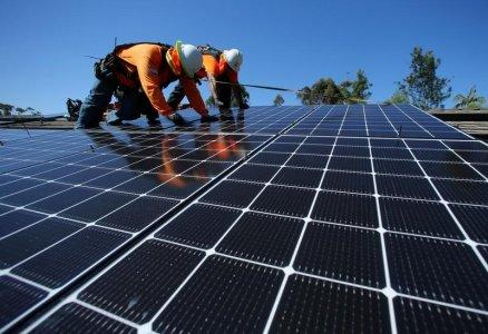 Solar installers from Baker Electric place solar panels on the roof of a residential home in Scripps Ranch, San Diego, California, U.S. October 14, 2016. REUTERS/Mike Blake/File Photo
