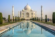"<p>The renowned marble-clad mausoleum in Agra was built as an act of love. Mughal Emperor Shah Jahan commissioned the <a href=""https://whc.unesco.org/en/list/252/"" rel=""nofollow noopener"" target=""_blank"" data-ylk=""slk:Taj Mahal"" class=""link rapid-noclick-resp"">Taj Mahal </a>in 1632 as monumental tomb for his beloved wife, Mumtaz Mahal, who died during childbirth. </p><p>One of the most impressive attributes of the Mughal structure is its seamless symmetry, from its minarets flanking the domed tomb to the central pool and gardens. Additionally, the minarets surrounding the tombs appear to be standing upright, but they actually lean outward to prevent them from damaging the main crypt in case of a disaster.</p>"