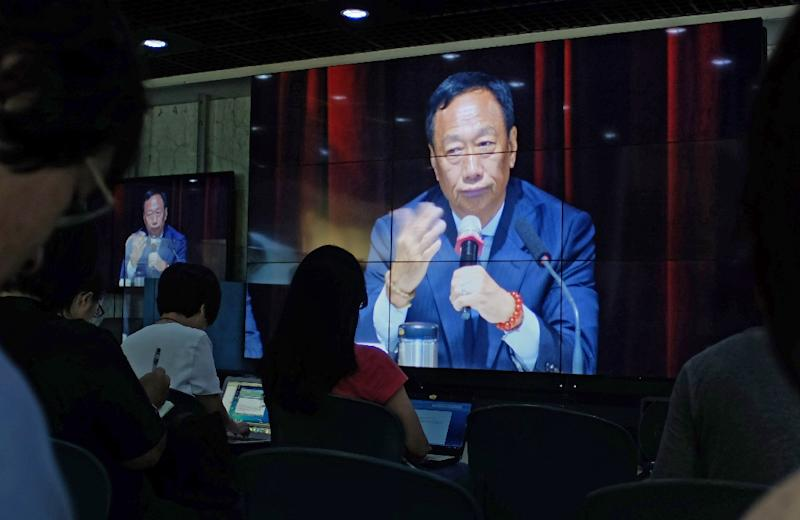 Journalists (in foreground) watch a large video screen showing Terry Gou, founder of Foxconn parent Hon Hai group, during a shareholders conference at the company's headquarters in Tucheng in New Taipei City on June 22, 2016 (AFP Photo/SAM YEH)