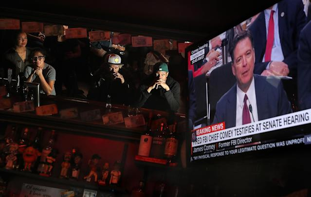 <p>Patrons at Ace's Bar watch a television broadcast of former FBI Director James Comey testify before the Senate Intelligence Committee on June 8, 2017 in San Francisco. (Photo: Justin Sullivan/Getty Images) </p>