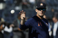 Houston Astros manager AJ Hinch (14) reaches for a ball before Game 3 of baseball's American League Championship Series against the New York Yankees, Tuesday, Oct. 15, 2019, in New York. (AP Photo/Matt Slocum)