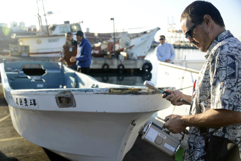 In this photo provided by the U.S. Coast Guard, Joshua Marvit, of the State of Hawaii Dept. of Health, tests a 16-foot skiff for radiation after the vessel was salvaged by the crew of the F/V Zephyr approximately 800 miles north of Honolulu, Friday, Oct. 5, 2012. The skiff was confirmed to have been debris from the 2011 Japan Tsunami by the Japanese Consulate, after they contacted the owner, through the Japanese Ministry of Foreign Affairs, and confirmed that they did not seek its return. (AP Photo/U.S. Coast Guard, Petty Officer 2nd Class Eric J. Chandler)