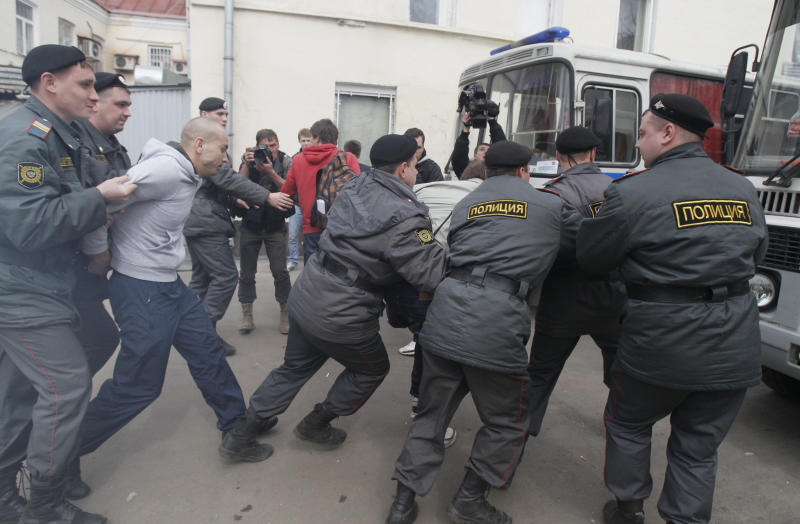 """Police detain supporters of Pussy Riot outside a court in Moscow, Russia, Thursday, April 19, 2012. Five members of the band Pussy Riot briefly seized the pulpit of Moscow's Christ the Savior Cathedral in February to chant """"Mother Mary, drive Putin away."""" Moscow court is set to consider extending the detention of three female punk rockers arrested after a surprise protest performance inside the country's main Orthodox cathedral. (AP Photo/Ivan Sekretarev)"""