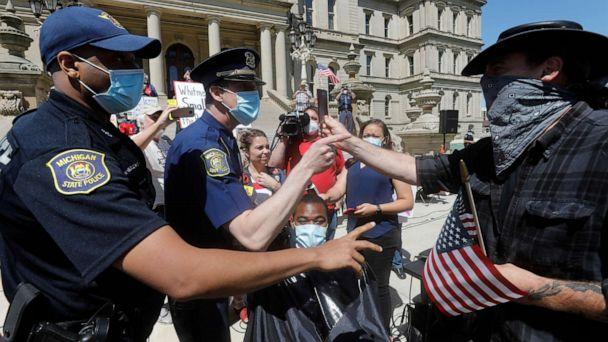PHOTO: A person tries to help Angela Rigas as she gets a ticket for being a disorderly person as she cuts hair at the Michigan Conservative Coalition organized 'Operation Haircut' outside the Michigan State Capitol in Lansing, Michigan on May 20, 2020. (Jeff Kowalsky/AFP via Getty Images)