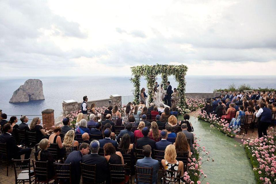 """<p>This wedding aisle and ceremonial chuppah in Capri was inspired by the bride's love of fashion—and a stunning runway show. """"Most aisles are straight, but [Jung Lee of] <a href=""""http://feteny.com/"""" rel=""""nofollow noopener"""" target=""""_blank"""" data-ylk=""""slk:Fête NY"""" class=""""link rapid-noclick-resp"""">Fête NY</a> created an organic pathway delineated with thousands of pale pink carnations, inspired by a photo of Tory Burch's autumn/winter 2018 fashion show,"""" said the bride. Situated (seemingly) on the edge of the earth, this ceremony was studded with thousands of flowers, allowing guests to feel as though they'd walked through a field to reach the couple's epic ceremony site. </p><p>Get the look by seeking inspiration from your favourite fashion shows when designing your aisle, whether it's Jacquemus' romantic catwalks in the lavender or wheat fields of the South of France, or Oscar de la Renta's grand showcase in the New York Public Library.</p><p>Pictured: <a href=""""https://www.harpersbazaar.com/wedding/photos/a27482104/jamie-bernfield-seth-birkan-wedding/"""" rel=""""nofollow noopener"""" target=""""_blank"""" data-ylk=""""slk:Jamie Bernfield and Seth Birkan's wedding in Capri"""" class=""""link rapid-noclick-resp"""">Jamie Bernfield and Seth Birkan's wedding in Capri</a>. Planning by Jung Lee of <a href=""""http://feteny.com/"""" rel=""""nofollow noopener"""" target=""""_blank"""" data-ylk=""""slk:Fête NY"""" class=""""link rapid-noclick-resp"""">Fête NY</a>.</p>"""
