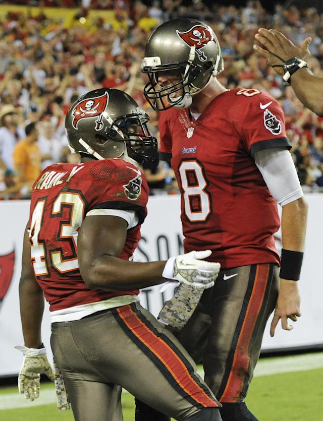Tampa Bay Buccaneers running back Bobby Rainey (43) celebrates a 31-yard run with quarterback Mike Glennon (8) during the second half of an NFL football game against the Miami Dolphins in Tampa, Fla., Tuesday, Nov. 12, 2013. Tampa Bay won the game 22-19.(AP Photo/Brian Blanco)