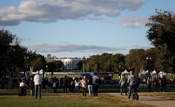 Bystanders look on as Marine One waits on the South Lawn at the White House.