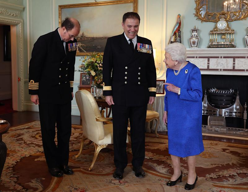Queen Elizabeth II receives Commodore Steven Moorhouse (centre, outgoing Commanding Officer, HMS Queen Elizabeth) and Captain Angus Essenhigh (incoming Commanding Officer), during a private audience in the Queen's Private Audience Room, at Buckingham Palace, London. PA Photo. Picture date: Wednesday March 18, 2019. Photo credit should read: Yui Mok/PA Wire