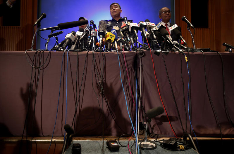 Over a dozen microphones are propped on a table as Malaysian police chief Khalid Abu Bakar answers questions from members of the media, raising their hands waiting their turn as seen in the shadows cast on stage during a press conference, Tuesday, March 11, 2014 in Sepang, Malaysia. One of the two men traveling on a missing Malaysia Airlines jetliner with a stolen passport was a 19-year-old Iranian man believed to be trying to migrate to Germany, and had no terror links, police said Tuesday. (AP Photo/Wong Maye-E)