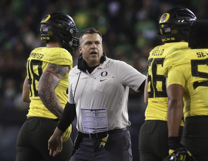 FILE - In this Saturday, Nov. 16, 2019 file photo, Oregon coach Mario Cristobal welcomes his team back to the sideline after a first-quarter score against Arizona in an NCAA college football game in Eugene, Ore. Oregon has won the past two Pac-12 championships and is poised to be in contention to win another. Coach Mario Cristobal has pulled in the conference's top recruiting class the past two seasons and the 2021 class was sixth nationally, including pro-style quarterback Ty Thompson, who will likely battle Anthony Brown for the starting spot. (AP Photo/Chris Pietsch, File)