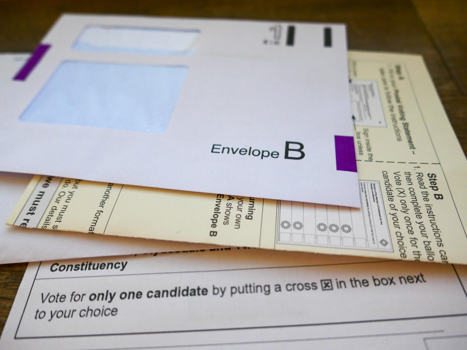 UK General Election postal vote ballot papers. The paperwork includes a return envelope, instructions on how to complete the postal vote and a ballot paper with constituency candidate names and details on how to vote for just one candidate by putting a cross in the box next to the voters choice.