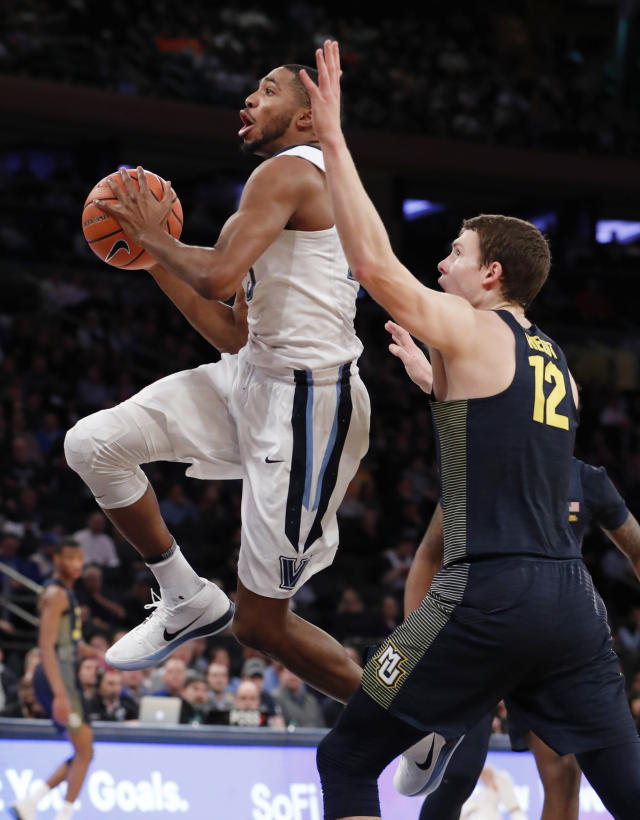 Villanova guard Mikal Bridges (25) goes to the basket in front of Marquette center Matt Heldt during the first half of an NCAA college basketball game in the quarterfinals of the Big East men's tournament in New York, Thursday, March 8, 2018. (AP Photo/Kathy Willens)