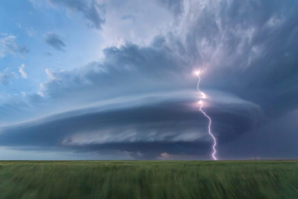 "According to NWF: A self-described ""adrenaline junkie,"" retired firefighter Laura Hedien has been chasing storms for 15 years across the Great Plains. With friends, she followed this one from Colorado into Kansas, where, toward nightfall, it shot lightning through a swirling ""spaceship"" of clouds. ""This is what we call a shoot 'n scoot,"" she says of the chase. ""These storms feel alive, morphing as they move. It's so exciting."" LAURA HEDIEN, 2020 National Wildlife® Photo Contest"