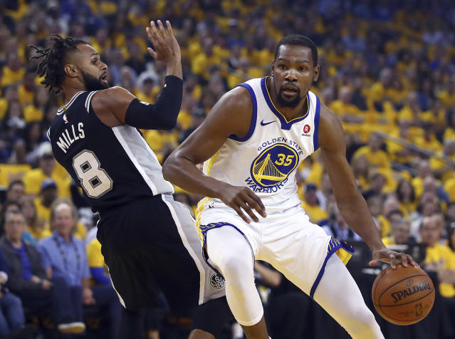 Golden State Warriors' Kevin Durant, right, drives the ball around San Antonio Spurs' Patty Mills (8) during the first half in Game 1 of a first-round NBA basketball playoff series Saturday, April 14, 2018, in Oakland, Calif. (AP Photo/Ben Margot)