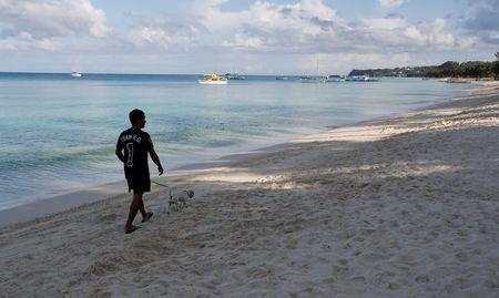 A resident walks his dog in an empty beach during the shutdown of the holiday island Boracay