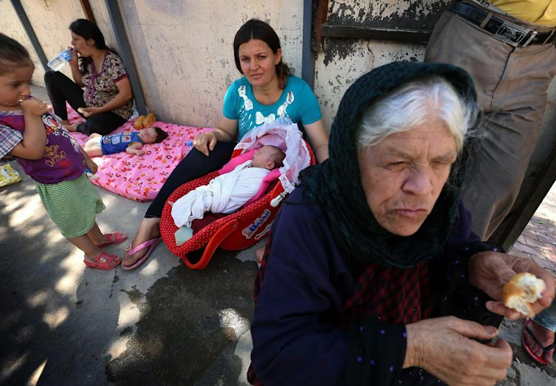 Iraqi Christians, who fled violence in the town of Qaraqosh, rest in the garden of Ainkawa's Saint Joseph church on August 12, 2014 on the outskirts of Arbil, the capital of the country's autonomous Kurdish region