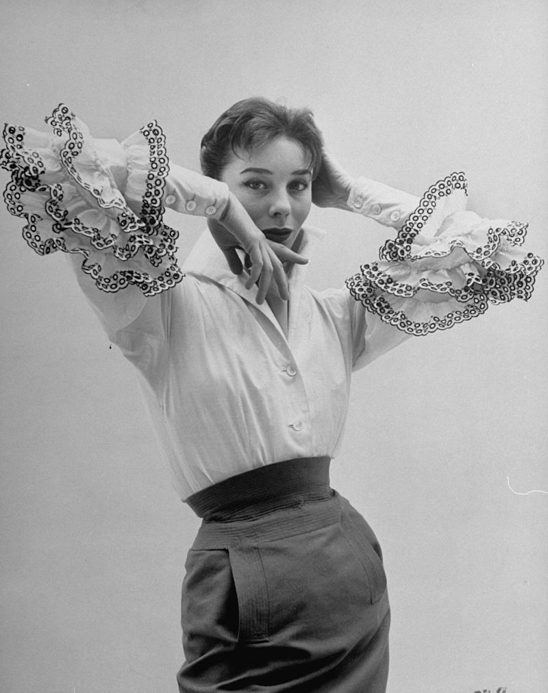 "Model Bettina Graziani wearing the ""<a href=""https://www.givenchy.com/america/en/maison-history-first-collection.html"" target=""_blank"">Bettina blouse</a>,"" a piece from Hubert de Givenchy's very first collection."