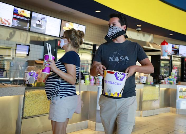 """Patrons carry popcorn and drinks into the first showing of """"Tenet"""" at Reading Cinemas Grossmont in La Mesa."""