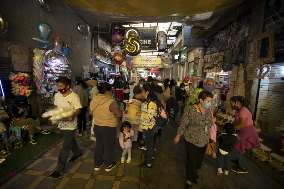 People shop at a market in downtown Mexico City, Friday, Oct. 30, 2020. Prior to the coronavirus pandemic, Mexico's economy was in recession, and that only deepened with the economic shutdown provoked by measures aimed at slowing the spread of COVID-19 during the second quarter. (AP Photo/Fernando Llano)