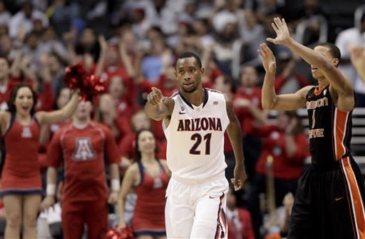 Arizona's Kyle Fogg points to his teammate after making a three-point basket during the second half of an NCAA college basketball game against the Oregon State in the semifinals of the Pac-12 Conference championship in Los Angeles, Friday, March 9, 2012. Standing at right is Oregon State's Jared Cunningham (AP Photo/Jae C. Hong)