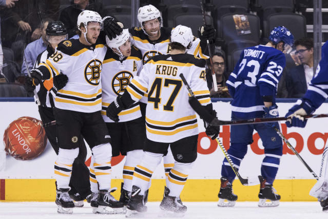 Boston Bruins' David Pastrnak (88) celebrates with teammates after scoring his first goal during second period NHL hockey action against the Toronto Maple Leafs, in Toronto on Monday, Nov. 26, 2018. (Chris Young/The Canadian Press via AP)