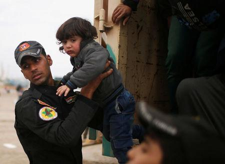 An Iraqi soldier helps a displaced child to get out of a truck as Iraqi forces battle with Islamic State militants, in western Mosul, Iraq March 28, 2017. REUTERS/Suhaib Salem