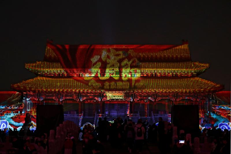 Visitors tour the Forbidden City projected with colorful lights during the Lantern Festival in Beijing, Tuesday, Feb. 19, 2019. (Photo: Andy Wong/AP)