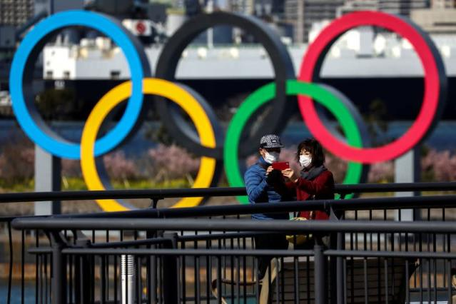 FILE PHOTO: People wearing protective face masks are seen in front of the Giant Olympic rings at the waterfront area at Odaiba Marine Park in Tokyo
