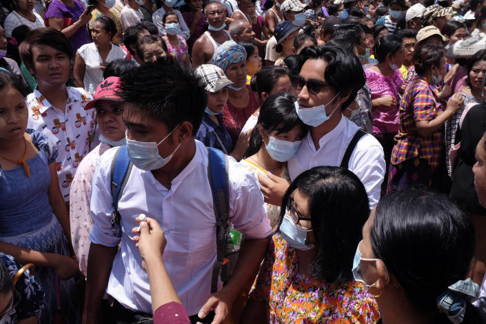 Zay Yar Lwin, center left in white, and Paing Pyo Min,center right in white, – both members of the Peacock Generation, a traditional theatrical troupe sentenced to prison in 2019 for their gibes about the military, walk through a crowd after their release from Insein prison in Yangon, Myanmar, Saturday, April 17, 2021. Myanmar's junta on Saturday announced it pardoned and released more than 23,000 prisoners to mark the new year holiday, but it wasn't immediately clear if they included pro-democracy activists who were detained in the wake of the February coup. (AP Photo)