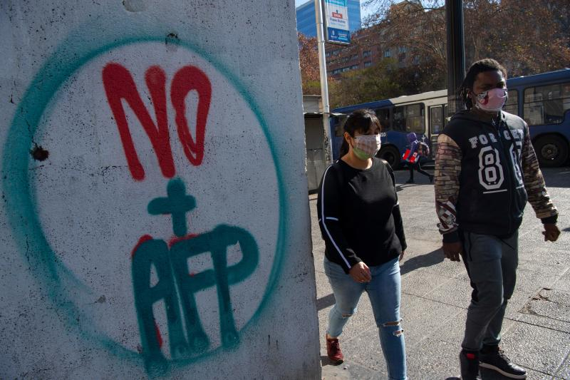 People pass by a graffiti against the Pension Fund Administration (AFP) in Santiago, on July 15, 2020. - The Chamber of Deputies will discuss Wednesday a bill that seeks to authorize, for the first time in Chile, affiliates of the AFP system to withdraw up to 10% of the funds due to the COVID-19 pandemic. (Photo by Martin BERNETTI / AFP) (Photo by MARTIN BERNETTI/AFP via Getty Images)