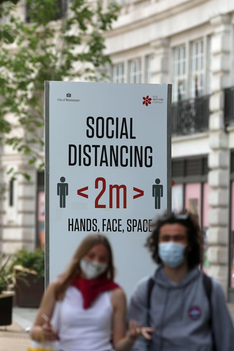 People in the street near a sign offering public health advice during the coronavirus pandemic (PA Wire)