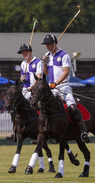 Prince William, the Duke of Cambridge, right, and Prince Harry in action during The Jerudong Trophy at Cirencester Park Polo Club in Gloucestershire Sunday July 14, 2013. Many in the British press have predicted that the first child of the prince and the Duchess of Cambridge, formerly known as Kate Middleton, was expected to arrive on Sunday but the prince was enjoying a game of polo against his brother Prince Harry at a charity event. (AP Photo/ Chris Ison, PA) UNITED KINGDOM OUT - NO SALES - NO ARCHIVES