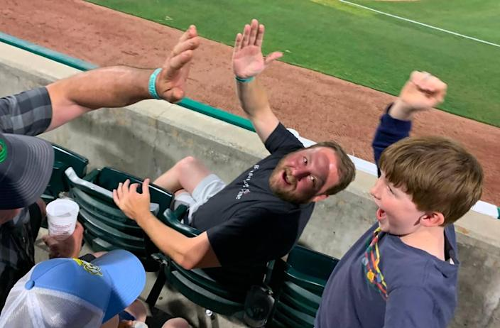 Brian Sharkey, far right, prepares to high-five his dad Ben Sharkey, center, and his friend's father, Brendan Sweeney, after the first home run of the Charleston RiverDogs 2021 season-opener.