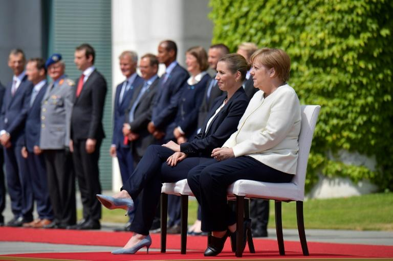 German Chancellor Angela Merkel and Denmark's Prime Minister Mette Frederiksen sat as they listened to the national anthems