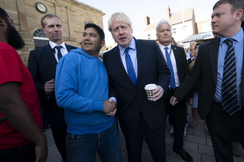 Britain's Prime Minister Boris Johnson shakes hands with a member of the public during a visit to Doncaster Market, in Doncaster, Northern England, Friday Sept. 13, 2019. Johnson will meet with European Commission president Jean-Claude Juncker for Brexit talks Monday in Luxembourg. The Brexit negotiations have produced few signs of progress as the Oct. 31 deadline for Britain's departure from the European Union bloc nears. ( AP Photo/Jon Super)