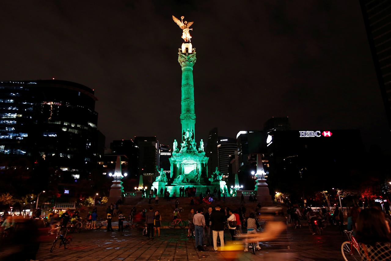 "People stand by ""Angel de la Independencia"" monument before the lights were turned off for Earth Hour in Mexico City, Mexico, March 25, 2017. REUTERS/Ginnette Riquelme"
