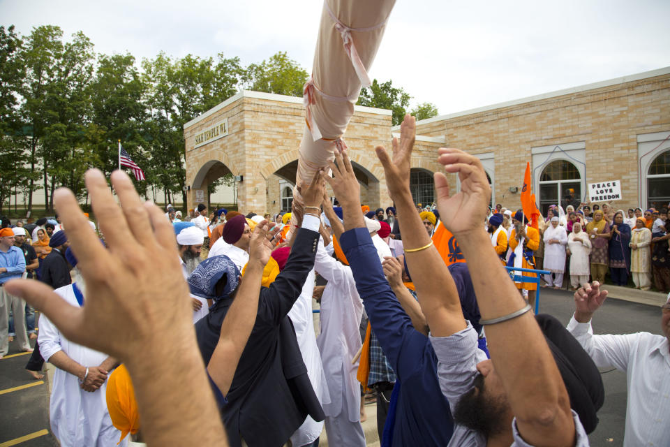 People attend a flag ceremony being held outside the Sikh Temple of Wisconsin in Oak Creek, Wis., Sunday, Aug. 12, 2012. More than 100 people gathered for the first Sunday prayer service since a white supremacist shot and killed six people there before fatally shooting himself. (AP Photo/Jeffrey Phelps)