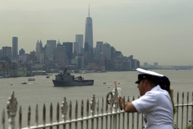 A sailor stands in Weehawken, New Jersey, to look at the USS Oak Hill, a Harpers Ferry-class dock landing ship of the United States Navy, as it arrives in New York Harbor for Fleet Week in New York May 21, 2014. REUTERS/Eduardo Munoz (UNITED STATES - Tags: MILITARY MARITIME)