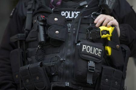 An armed police officer rests his hand on a taser outside the Ministry of Defence in London, Britain
