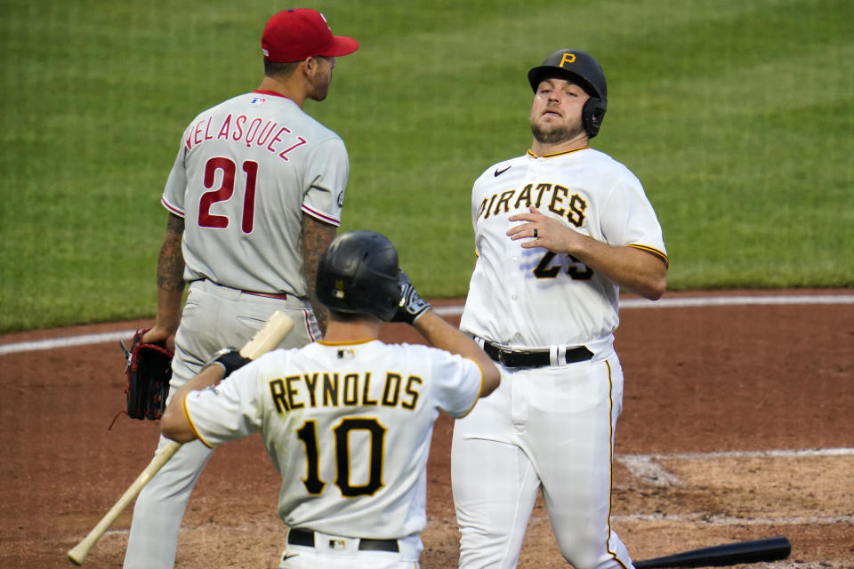 Pittsburgh Pirates' Wil Crowe, right, scores on a double by Ke'Bryan Hayes off Philadelphia Phillies starting pitcher Vince Velasquez (21) during the second inning of a baseball game in Pittsburgh, Friday, July 30, 2021. (AP Photo/Gene J. Puskar)