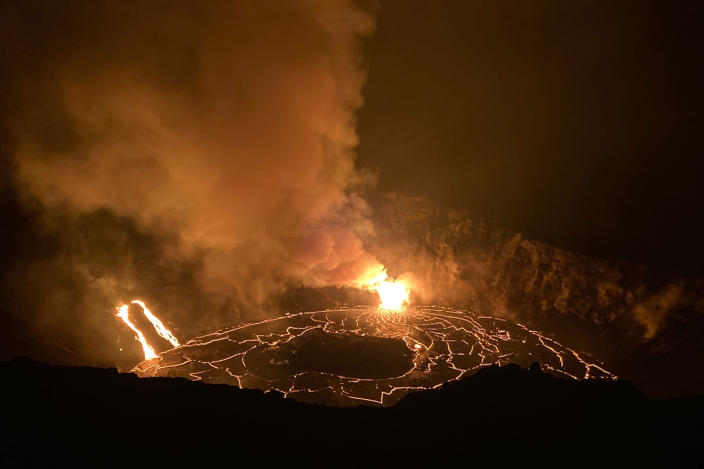 In this photo provided by the U.S. Geological Survey, a lava lake continues its rise in the crater of Hawaii's Kilauea volcano on Wednesday, Dec. 23, 2020. Lava is rising more than 3 feet per hour in the deep crater of a Hawaii volcano that began erupting over the weekend. The U.S. Geological Survey says Kilauea volcano within Hawaii Volcanoes National Park on the Big Island was gushing molten rock from at least two vents inside its summit crater. (H. Dietterich/U.S. Geological Survey via AP)