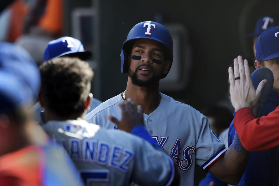 Texas Rangers' Jose Trevino is congratulated after scoring against the Baltimore Orioles in the seventh inning of a baseball game Sunday, Sept. 26, 2021, in Baltimore. (AP Photo/Gail Burton)