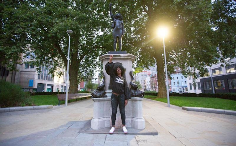 BLM protester Jen Reid stands in front of a statue of her, installed at the site previously occupied by slave trader Edward Colston in Bristol.