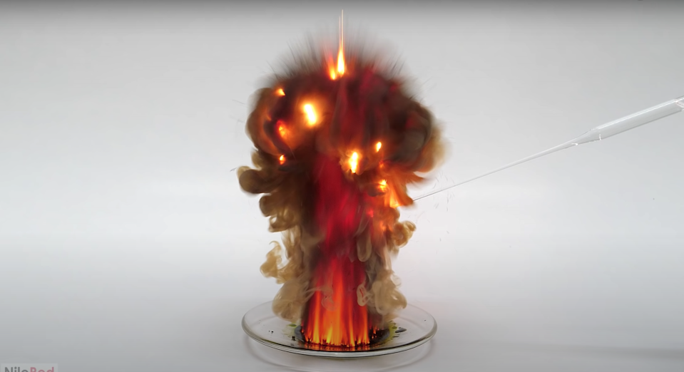 Manganese heptoxide, a highly volatile liquid, explodes into a small fiery ball of orange and reds with smoke on a small dish