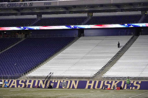 FILE - One person stands in the seats during the playing of the national anthem before an NCAA college football game between Washington and Arizona in Seattle, in this Saturday, Nov. 21, 2020, file photo. Washington has pulled out of the Pac-12 football championship game due to COVID-19 issues in the Huskies program, and Oregon will now play No. 13 USC for the conference title on Friday instead. Washington (3-1) announced Monday, Dec. 14, 2020, it is withdrawing from the championship game after determining the Huskies did not have at least 53 scholarship players available and did not meet the minimum number of scholarship athletes at specific positions. (AP Photo/Elaine Thompson, File)