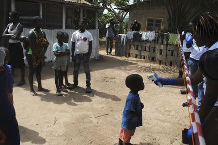 Health workers take temperature of boy who came in contact with woman who died of Ebola virus in Paynesville neighborhood of Monrovia