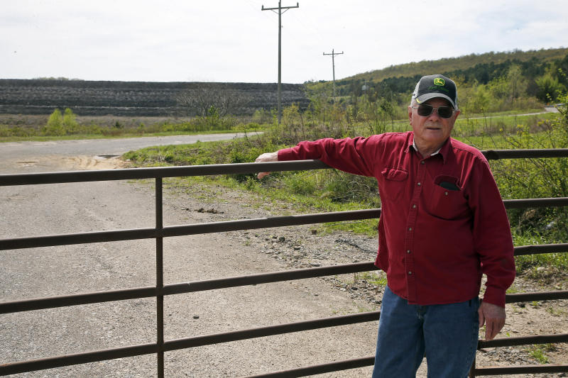 "In this April 8, 2019, photo, Tim Tanksley, who has been fighting for years trying to convince Oklahoma lawmakers to crack down on the coal ash dumping, stands outside a dump site in Bokoshe, Okla. President Donald Trump's EPA has approved Oklahoma to be the first state to take over permitting and enforcement on coal-ash sites. ""They're going to do absolutely nothing,"" Tanksley said. (AP Photo/Sue Ogrocki)"